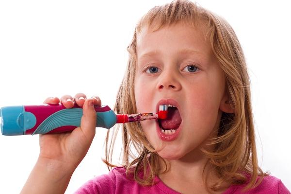 девочка 5-ти лет чистит зубы электрической щеткой