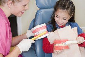 стоматолог учит ребенка чистить зубы самостоятельно